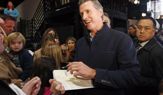 """FILE - In this Jan. 6, 2019 file photo, Gov.-elect Gavin Newsom autographs a copy of his book """"Citizenville"""" for a wellwisher while attending a pre-inaugural Family Event held at the California Railroad Museum in Sacramento, Calif. Gov. Newsom is preparing to release his first state budget, offering his clearest outline yet of his plan to significantly boost spending on services for children while maintaining his promise to be fiscally prudent. Newsom plans to discuss his proposal during a news conference in Sacramento on Thursday, Jan. 10, 2019.  (AP Photo/Rich Pedroncelli, File)"""