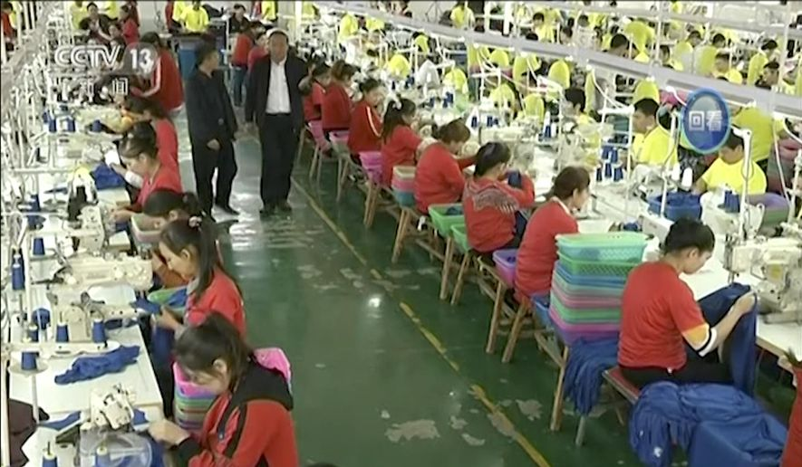 In this file image from undated video footage run by China's CCTV via AP Video, Muslim trainees work in a garment factory at the Hotan Vocational Education and Training Center in Hotan, Xinjiang, northwest China. A U.S. company that stocks college bookstores with T-shirts and other team apparel cut ties Wednesday, Jan. 9, 2019, with a Chinese company that drew workers from an internment camp holding targeted members of ethnic minority groups. (CCTV via AP Video, File)