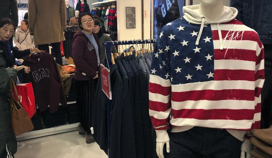 Chinese shoppers sort through merchandise at the Gap's flagship store in Beijing. Chinese leaders believe they are on the road to victory over the U.S. and will to do anything to get there. (Associated Press/File)