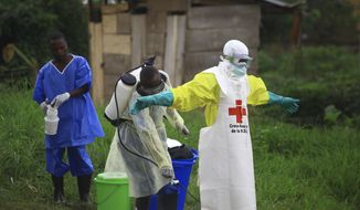 In this Sunday, Sept 9, 2018, photo, a health worker sprays disinfectant on his colleague after working at an Ebola treatment center in Beni, Eastern Congo. (AP Photo/Al-hadji Kudra Maliro) **FILE**