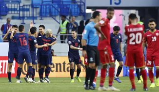 Thailand players, left, celebrate after they beat Bahrain 1-0, during the AFC Asian Cup group A soccer match between Bahrain and Thailand at Al Maktoum Stadium in Dubai, United Arab Emirates, Thursday, Jan. 10, 2019. (AP Photo/Hassan Ammar)