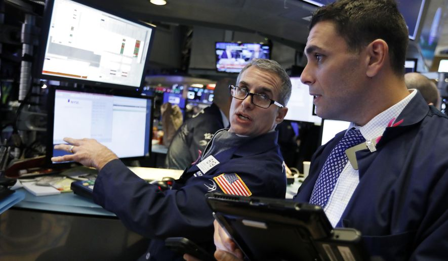 FILE- In this Jan. 3, 2019, file photo specialist Anthony Rinaldi, left, works at his post on the floor of the New York Stock Exchange. The U.S. stock market opens at 9:30 a.m. EST on Thursday, Jan. 10. (AP Photo/Richard Drew, File)