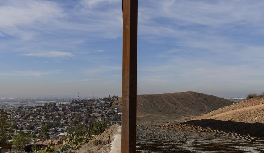This Saturday, Dec. 22, 2018, file photo shows Tijuana, Mexico, left, and San Diego, Calif., separated by a U.S. border fence. (AP Photo/Daniel Ochoa de Olza)