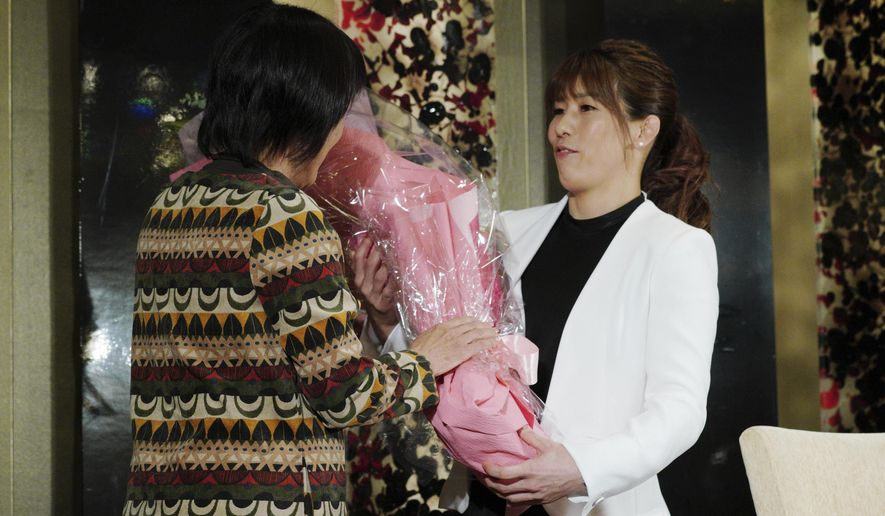 Japan's three-time Olympic wrestling champion Saori Yoshid, right, receives a bouquet of flowers by her mother Yukiyo Yoshida at the end of her press conference in Tokyo Thursday, Jan. 10, 2019. Yoshida announced her retirement, saying it's time for the next generation of wrestlers to take the stage at the 2020 Tokyo Olympics. (AP Photo/Eugene Hoshiko)