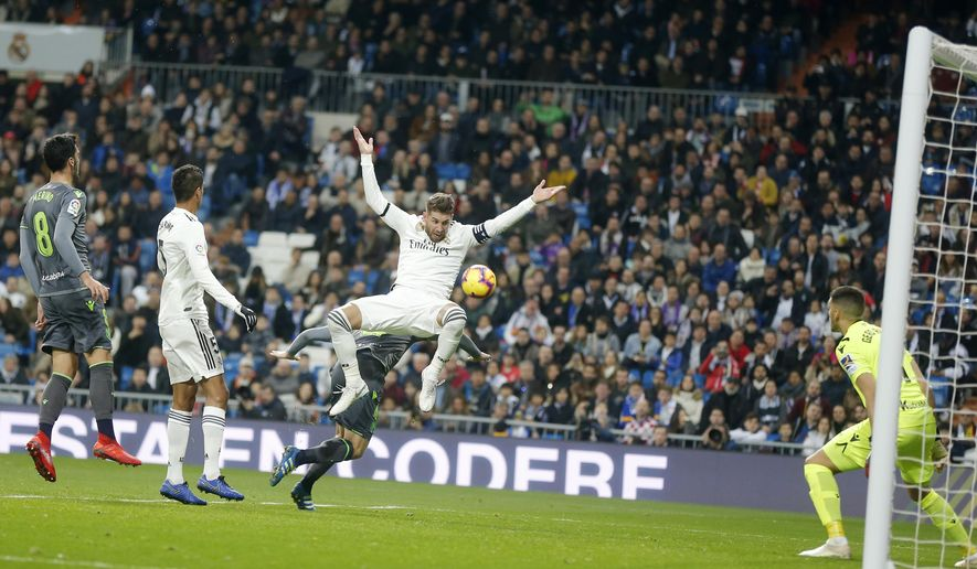 Real Madrid's Sergio Ramos jumps with Real Sociedad's Asier Illarramendi during a Spanish La Liga soccer match between Real Madrid and Real Sociedad at the Santiago Bernabeu stadium in Madrid, Spain, Sunday, Jan. 6, 2019. (AP Photo/Paul White)