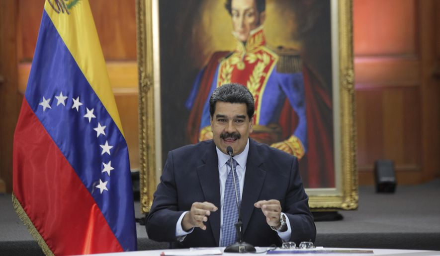 Venezuela's President Nicolas Maduro holds a press conference with foreign media at Miraflores presidential palace where an image of Venezuelan independence hero Simon Bolivar is displayed in Caracas, Venezuela, Wednesday, Jan. 9, 2019. Maduro will be sworn in for a second, six-year term on Thursday. (AP Photo/Boris Vergara)