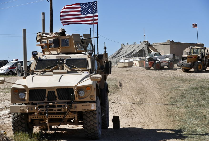 In this Wednesday, April 4, 2018, photo, a U.S. soldier, left, sits on an armored vehicle behind a sand barrier at a newly installed position near the front line between the U.S-backed Syrian Manbij Military Council and the Turkish-backed fighters, in Manbij, north Syria. An American military official said Friday, Jan. 11, 2019 that the U.S.-led military coalition has begun the process of withdrawing troops from Syria. (AP Photo/Hussein Malla) **FILE**
