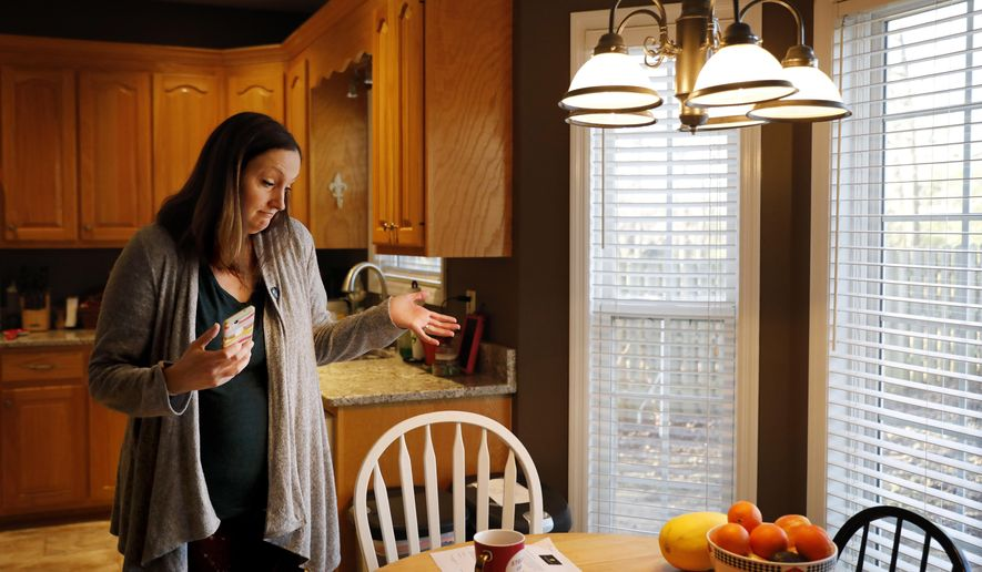 Katie Barron gestures while looking at a pay increase notice for her children's day care, in her home in Madison, Ala., Wednesday, Jan. 9, 2019. Barron's husband is a National Weather Service meteorologist forced to work without pay during the shutdown because his job is classified as essential. They've put off home and car maintenance, but the $450-a-week bill for day care still has to be paid, as do the mortgage and utility bills. (AP Photo/David Goldman)