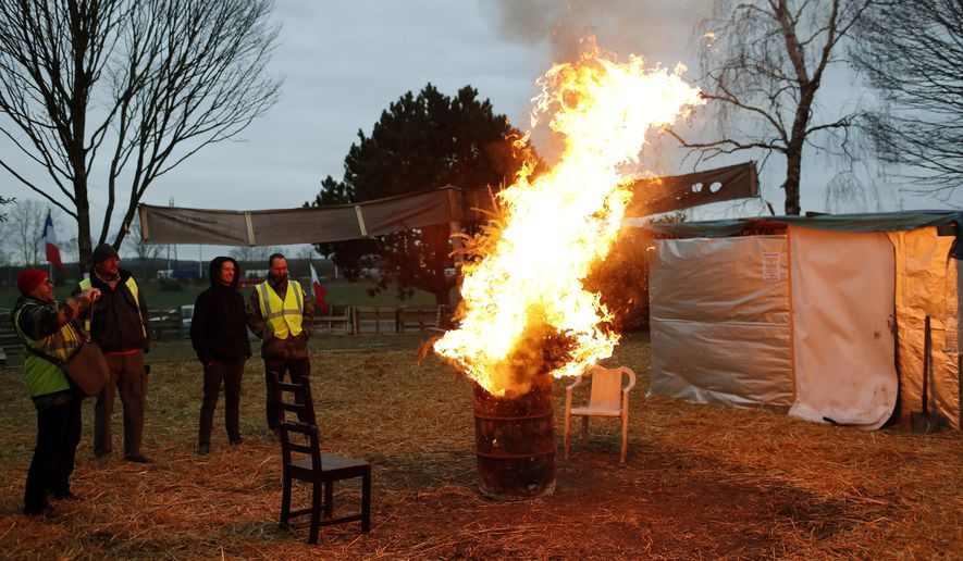 Protesters wearing yellow vests stand next to a fire in a makeshift camp on a roundabout near Senlis, north of Paris, Thursday, Jan. 10, 2019. (AP Photo/Thibault Camus)
