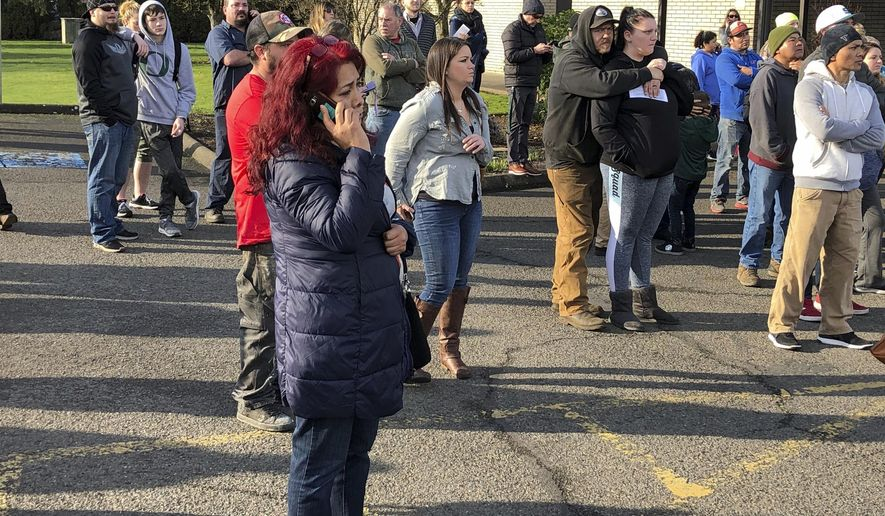 Parents of students at Cascade Middle School wait to be reunited with their children in Eugene, Ore., Friday, Jan. 11, 2019. A suspect was shot Friday at an Oregon middle school but no students or teachers were hurt, police said. Students were locked in classrooms and no one was being allowed into the building during the lockdown, Eugene police Lt. Jennifer Bills told reporters at Cascade Middle School. The district said in the statement that students would be released at 3 p.m. through the school's side exits and should be picked up at nearby St. Mark's Catholic Church. (AP Photo/Andrew Selsky)
