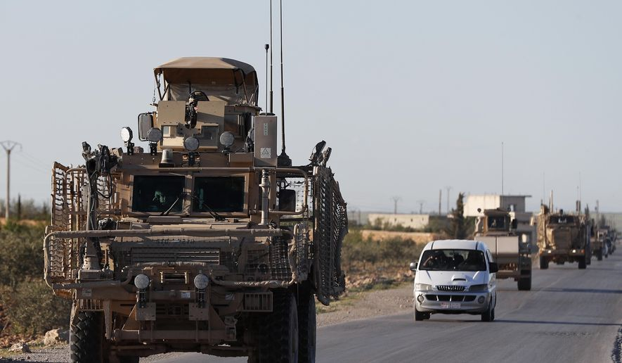 In this Saturday, March 31, 2018, file photo, a convoy of U.S. troops drive along a road leading to the front line with Turkish-backed fighters, in Manbij, north Syria. An American military official said Friday, Jan. 11, 2019, that the U.S.-led military coalition has begun the process of withdrawing troops from Syria. (AP Photo/Hussein Malla, File)