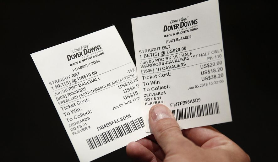 FILE - In this June 5, 2018, file photo, John Celatka displays a pair of receipts for bets he placed on an MLB baseball game and an NBA basketball game, inside the Race and Sports Book at Dover Downs Hotel and Casino in Dover, Del. A new, gambling-focused telecast of Washington Wizards games is just the appetizer to what the team and its TV partner hope will be a more substantial main course: giving fans the ability to place bets in real time while watching games at home. Whether that idea comes to fruition will depend on laws in the states where Wizards games are shown on the regional network NBC Sports Washington. But the concept shows how legal sports betting continues to change the way sports are presented to the public. (AP Photo/Patrick Semansky, File)