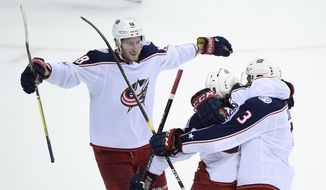 Columbus Blue Jackets left wing Artemi Panarin (9), of Russia, celebrates his goal with defenseman Seth Jones (3) and center Pierre-Luc Dubois (18) during overtime of an NHL hockey game against the Washington Capitals, Saturday, Jan. 12, 2019, in Washington. (AP Photo/Nick Wass) ** FILE **