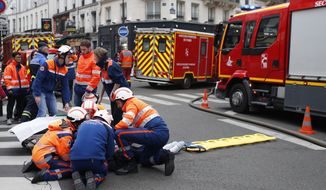 Firefighters tends to a wounded person near the site of a gas leak explosion in Paris, France, Saturday, Jan. 12, 2019. A powerful explosion and fire apparently caused by a gas leak at a Paris bakery Saturday injured several people, blasted out windows and overturned cars, police said. (AP Photo/Thibault Camus)