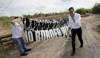 "FILE - In this Saturday, Jan. 6, 2018, file photo, Texas Democratic Congressman Beto O'Rourke, right, passes a ""No Border Wall"" sign during a visit to the National Butterfly Center in Mission, Texas, a possible location for a border wall. President Donald Trump is not giving up on his demands for $5.7 billion to build a wall along the U.S.-Mexico border, saying a physical barrier is central to any strategy for addressing the security and humanitarian crisis at the southern border. Democrats argue that funding the construction of a steel barrier along roughly 234 miles will not solve the problems. (AP Photo/Eric Gay, File) **FILE**"