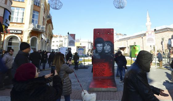 People take pictures of exhibits at the Art Liberte exhibition, the first traveling exhibition to mark the 30 years anniversary of fall of the Berlin wall in the town of Plovdiv ahead of the opening ceremony of Plovdiv as one of European Capital of Culture, Bulgaria, Saturday, Jan. 12, 2019. Plovdiv is the first Bulgarian town named to celebrate the most prestigious cultural initiative of the European Union, along with the Italian city of Matera as the twin European Capital of Culture for 2019. (AP Photo/STR)
