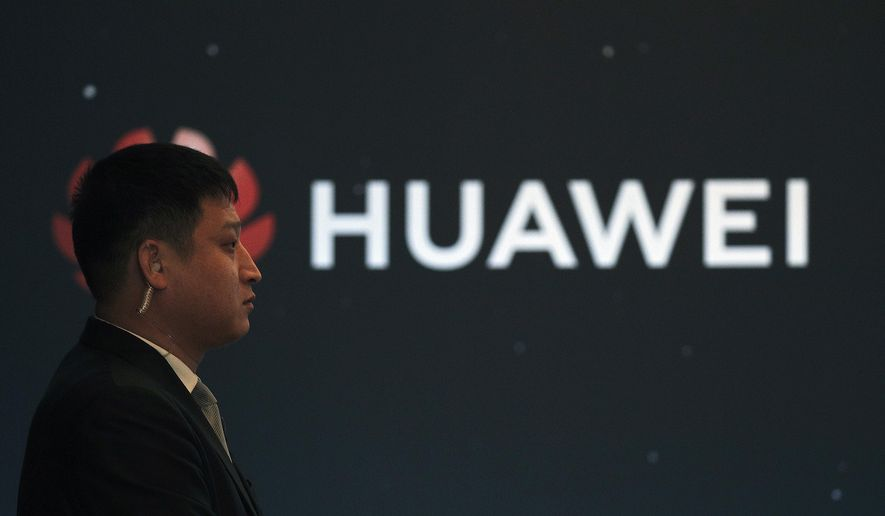 "In this Jan. 9, 2019, photo, a security guard stands near the Huawei company logo during a new product launching event in Beijing. The Chinese Foreign Ministry said late Friday, Jan. 11, 2019, it is ""closely following the detention of Huawei employee Wang Weijing"" on charges of allegedly spying for China, and has asked Poland to ""handle the case lawfully, fairly, properly and to effectively guarantee the legitimate rights of the person, his safety and his humanitarian treatment,"" according to state broadcaster CCTV. (AP Photo/Andy Wong)"