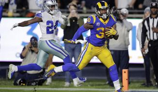 Los Angeles Rams running back Todd Gurley scores past Dallas Cowboys cornerback Chidobe Awuzie during the first half in an NFL divisional football playoff game Saturday, Jan. 12, 2019, in Los Angeles. (AP Photo/Jae C. Hong)