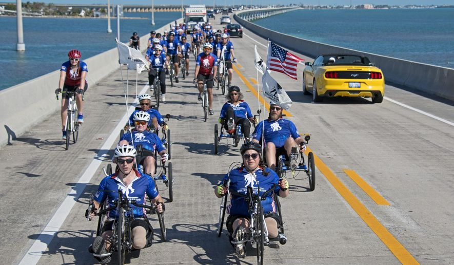 In this photo provided by the Florida Keys News Bureau, injured military personnel including Army Staff Sgt. Sam Oelke, left, retired Air Force Staff Sgt. Jennifer Caudillo, right, and other wounded military personnel ride bicycles on the Seven Mile Bridge during the Florida Keys Soldier Ride Friday, Jan. 11, 2019, near Marathon, Fla. Some 45 men and women are riding bicycles down segments of the Florida Keys Overseas Highway as a facet of an effort organized by the Wounded Warrior Project to raise public awareness and support for the needs of severely injured members of the U.S. military. (Andy Newman/Florida Keys News Bureau via AP)