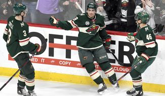 Minnesota Wild's Charlie Coyle (3) and Jared Spurgeon (46) move in to celebrate the goal of Luke Kunin, center, against the Detroit Red Wings in the first period of an NHL hockey game Saturday, Jan. 12, 2019, in St. Paul, Minn. (AP Photo/Tom Olmscheid)