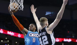 Oklahoma City Thunder guard Russell Westbrook (0) drives to the basket past San Antonio Spurs forward Davis Bertans (42) in the first half of an NBA basketball game in Oklahoma City, Saturday, Jan. 12, 2019. (AP Photo/Sue Ogrocki)