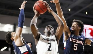 Cincinnati's Keith Williams (2) shoots against Connecticut's Isaiah Whaley (5) and Jalen Adams, left, in the first half of an NCAA college basketball game, Saturday, Jan. 12, 2019, in Cincinnati. (AP Photo/John Minchillo)
