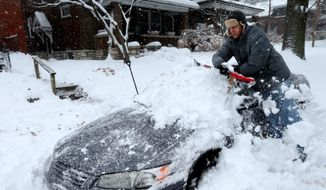 Jeff Clifford digs out his girlfriend's car from a pile of snow on Saturday in St. Louis. More than 800 snow-related crashes occurred this weekend in Missouri. (Associated Press)