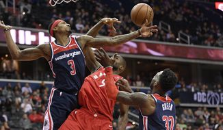 Washington Wizards guard Bradley Beal (3) and forward Jeff Green (32) battle for the rebound against Toronto Raptors forward Serge Ibaka (9) during the first half of an NBA basketball game, Sunday, Jan. 13, 2019, in Washington. (AP Photo/Nick Wass)