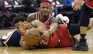 Washington Wizards guard Bradley Beal, top, battles for the ball against Toronto Raptors guard Kyle Lowry during the second half of an NBA basketball game, Sunday, Jan. 13, 2019, in Washington. (AP Photo/Nick Wass)
