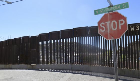 FILE - This March 9, 2016, file photo, shows a stop sign in front of the international border fence in Nogales, Ariz. Arizona Gov. Doug Ducey says building a wall isn't the only way to provide security along the U.S.-Mexico border. Ducey made border security a key issue of his 2018 campaign for re-election, and during his first term created the multi-agency Arizona Border Strike Force to focus on border area crime, especially drug smuggling. (AP Photo/Astrid Galvan, File)