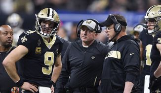 New Orleans Saints quarterback Drew Brees (9) talks with head coach Sean Payton, right, and offensive coordinator Pete Charmichael, in the first half of an NFL divisional playoff football game against the Philadelphia Eagles, in New Orleans, Sunday, Jan. 13, 2019. (AP Photo/Bill Feig) **FILE**