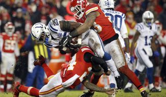Kansas City Chiefs linebacker Anthony Hitchens, top, and safety Jordan Lucas (24) tackle Indianapolis Colts running back Marlon Mack (25) during the second half of an NFL divisional football playoff game in Kansas City, Mo., Saturday, Jan. 12, 2019. (AP Photo/Charlie Riedel)