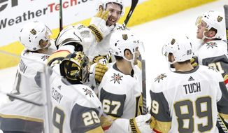 Vegas Golden Knights defenseman Shea Theodore,top center, celebrates with teammates after his goal against the Chicago Blackhawks during the overtime period of an NHL hockey game Saturday, Jan. 12, 2019, in Chicago. (AP Photo Nuccio DiNuzzo)
