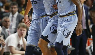 Memphis Grizzlies center Joakim Noah, left, and Memphis Grizzlies forward Justin Holiday, right, carry off Memphis Grizzlies forward Kyle Anderson, center, in the first half of an NBA basketball game against the Miami Heat, Saturday, Jan. 12, 2019, in Miami. (AP Photo/Brynn Anderson)