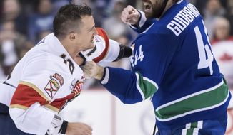Vancouver Canucks' Erik Gudbranson, right, and Florida Panthers' Micheal Haley fight during the first period of an NHL hockey game in Vancouver, British Columbia, Sunday, Jan. 13, 2019. (Darryl Dyck/The Canadian Press via AP)