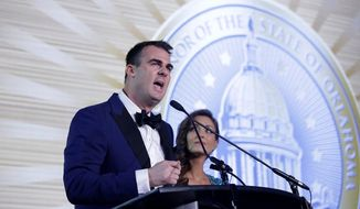 Oklahoma Republican Gov.-elect Kevin Stitt with his wife Sarah Stitt at his side speaks at his Pre-inaugural Redbud Ball at the Cox Business Center Saturday, Jan. 12, 2019, in Tulsa, Okla. Stitt will be sworn in to office Monday. (Mike Simons/Tulsa World via AP)