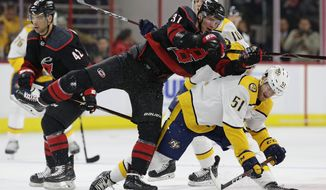 Carolina Hurricanes' Andrei Svechnikov (37), of Russia, collides with Nashville Predators' Austin Watson (51) during the second period of an NHL hockey game in Raleigh, N.C., Sunday, Jan. 13, 2019. (AP Photo/Gerry Broome)