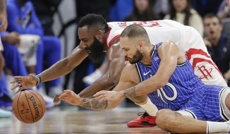 Houston Rockets' James Harden, left, and Orlando Magic's Evan Fournier (10) go after the ball during the second half of an NBA basketball game, Sunday, Jan. 13, 2019, in Orlando, Fla. (AP Photo/John Raoux)
