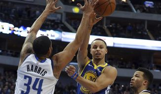 Golden State Warriors guard Stephen Curry (30) passes the ball around Dallas Mavericks guard Devin Harris (34) in the first half of an NBA basketball game Sunday, Jan. 13, 2019, in Dallas. (AP Photo/Richard W. Rodriguez)