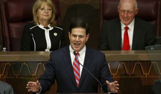 Arizona Republican Gov. Doug Ducey, center, speaks during his state of the state address as he talks about Arizona's economy, new jobs, and the state revenue as Senate president Karen Fann,  R-Prescott, left, and House Speaker Rusty Bowers, R-Mesa, right, listen Monday, Jan. 14, 2019, in Phoenix. (AP Photo/Ross D. Franklin)