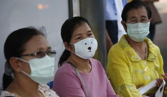 Women protective mask at the bus stop in heavy air pollution in Bangkok, Thailand, Monday, Jan. 14, 2019. Unusually high levels of smog worsened by weather patterns are raising alarm across Asia. (AP Photo/Sakchai Lalit)