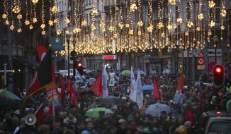 People march under rain during a demonstration in support of migrant people seeking to enter Europe, in Brussels, Saturday, Jan. 12, 2019. (AP Photo/Francisco Seco)