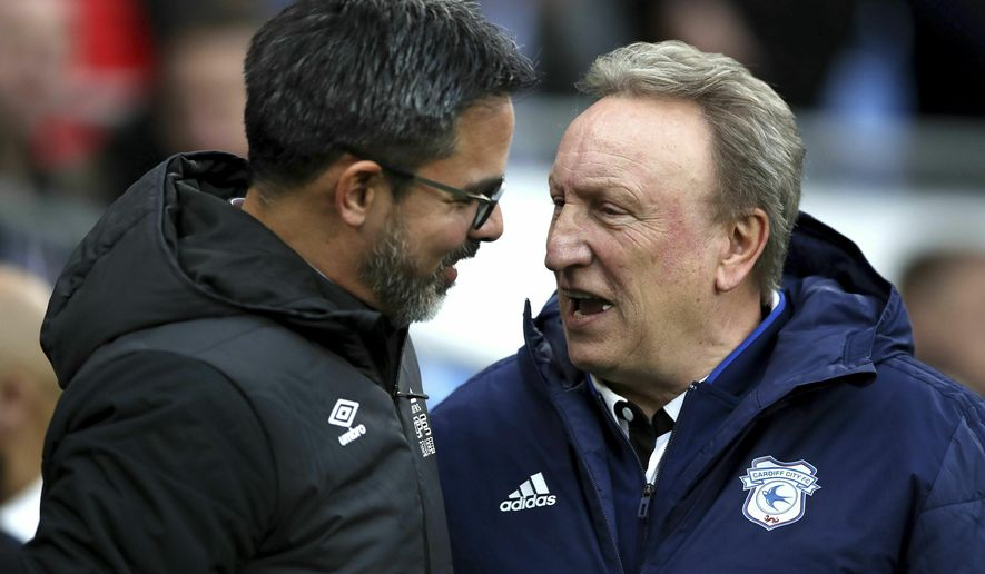 Huddersfield Town manager David Wagner, left, greets Cardiff City manager Neil Warnock during the English Premier League soccer match between Cardiff City and Huddersfield Town at the Cardiff City Stadium, Cardiff, Wales. Saturday, Jan. 12, 2019. (Nick Potts/PA via AP)