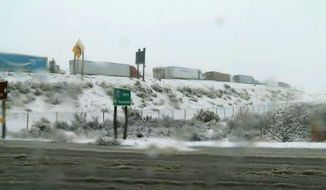 In this photo provided by KGET-TV, a line of big rigs are stalled on Interstate 5 where it has been closed due to snow at Tejon Pass, an area known as the Grapevine, at Gorman in the Tehachapi Mountains of Southern California Monday, Jan. 14, 2019. The first in a series of Pacific storms is moving across Southern California, where downpours could unleash mud and debris flows from large wildfire burn scars. (KGET-TV via AP)