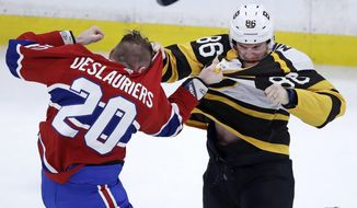 Boston Bruins defenseman Kevan Miller, right, fights Montreal Canadiens left wing Nicolas Deslauriers (20) during the first period of an NHL hockey game in Boston, Monday, Jan. 14, 2019. (AP Photo/Charles Krupa)