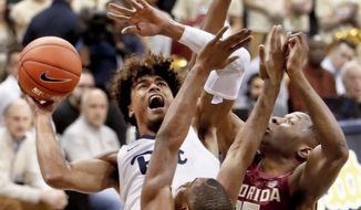 Pittsburgh's Malik Ellison, left, shoots as Florida State's Mfiondu Kabengele (25) and Trent Forrest, center defend during the first half of an NCAA college basketball game, Monday, Jan. 14, 2019, in Pittsburgh. (AP Photo/Keith Srakocic)