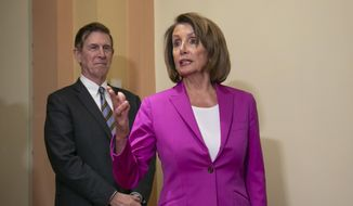 Speaker of the House Nancy Pelosi, D-Calif., joined at left by Rep. Don Beyer D-Va., talks to reporters after signing a House-passed a bill requiring that all government workers receive retroactive pay after the partial shutdown ends, at the Capitol in Washington, Friday, Jan. 11, 2019. (AP Photo/J. Scott Applewhite)