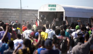 In this Dec. 10, 2018, file photo, police guard an alleged gang member to keep the crowd from attacking him outside a police station in the La Saline slum of Port-au-Prince, Haiti. Residents believe the arrested man is one of the perpetrators of a Nov. 13 massacre that killed at least 20 people in La Saline slum. (AP Photo/Dieu Nalio Chery)