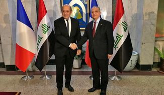 Iraqi Foreign Minister Mohamed Alhakim, right, shakes hands with visiting French Foreign Minister Jean-Yves Le Drian, in Baghdad, Iraq, Monday, Jan. 14, 2019. (AP Photo/Ali Abdul Hassan)