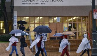 Los Angeles Unified District teacher brave the pouring rain to join in a picket line during a citywide teacher strike in front of Los Angeles High School on Monday, Jan. 14, 2019. Tens of thousands of Los Angeles teachers went on strike Monday after contentious contract negotiations failed in the nation's second-largest school district. (AP Photo/Richard Vogel)